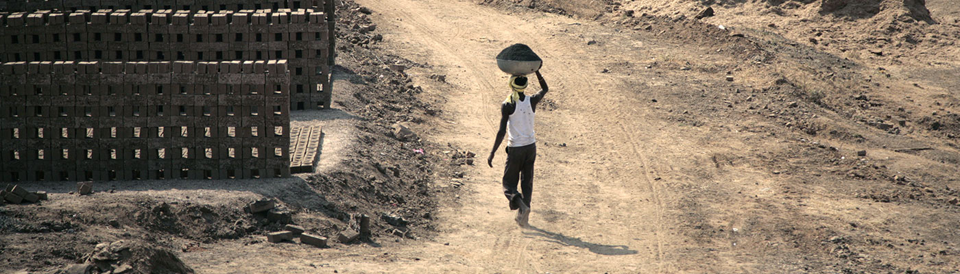 Person walking through dusty land carrying work materials on their head
